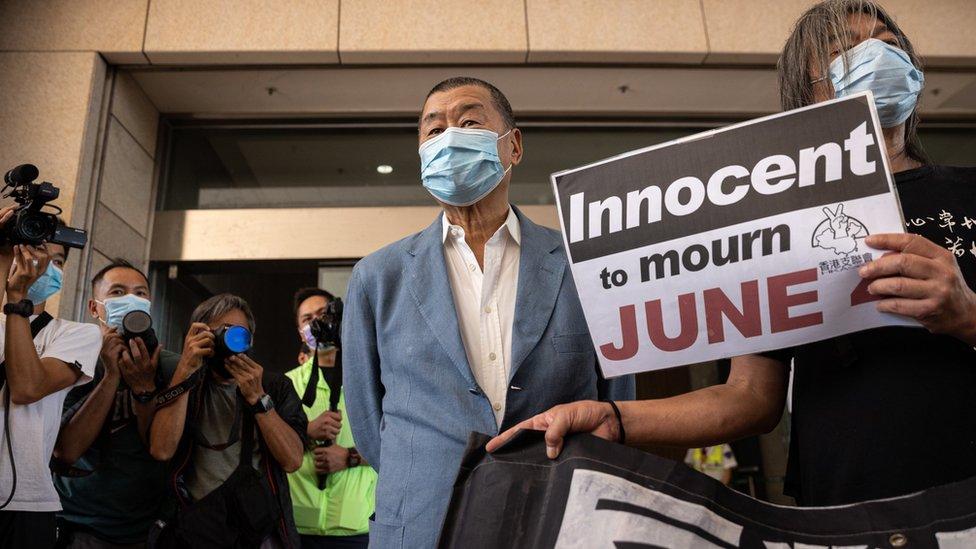 黎智英(中)與手持抗議標語的梁國雄(右)在香港西九龍法院大樓外讓媒體記者拍照(15/10/2020)