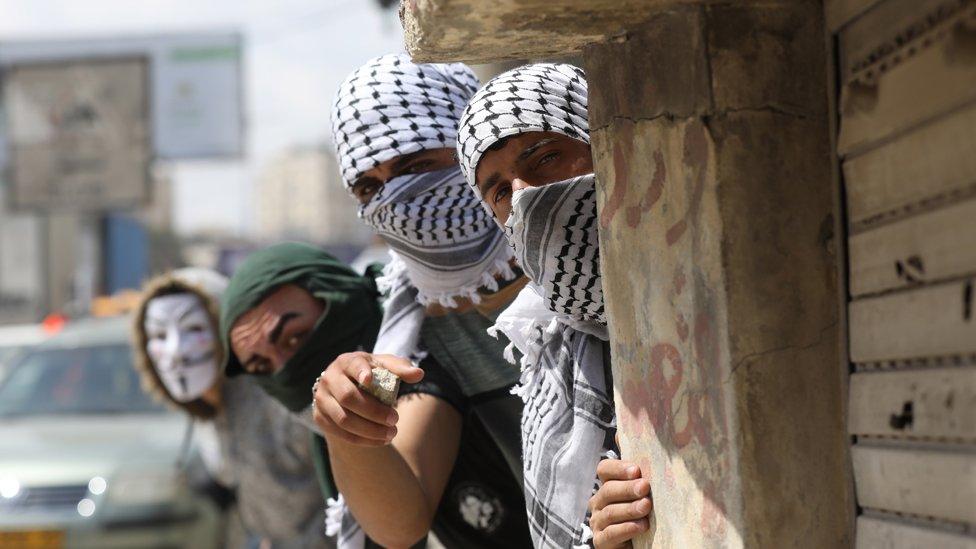 Jóvenes palestinos con el rostro cubierto, se esconden detrás de una pared