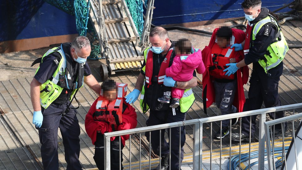 Three young children and a woman (right), thought to be a migrants, are brought ashore by Border Force officers at Dover marina in Kent