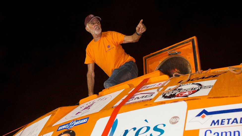 Jean-Jacques Savin is seen on top of his custom-made barrel after landing on the French Caribbean island of Martinique