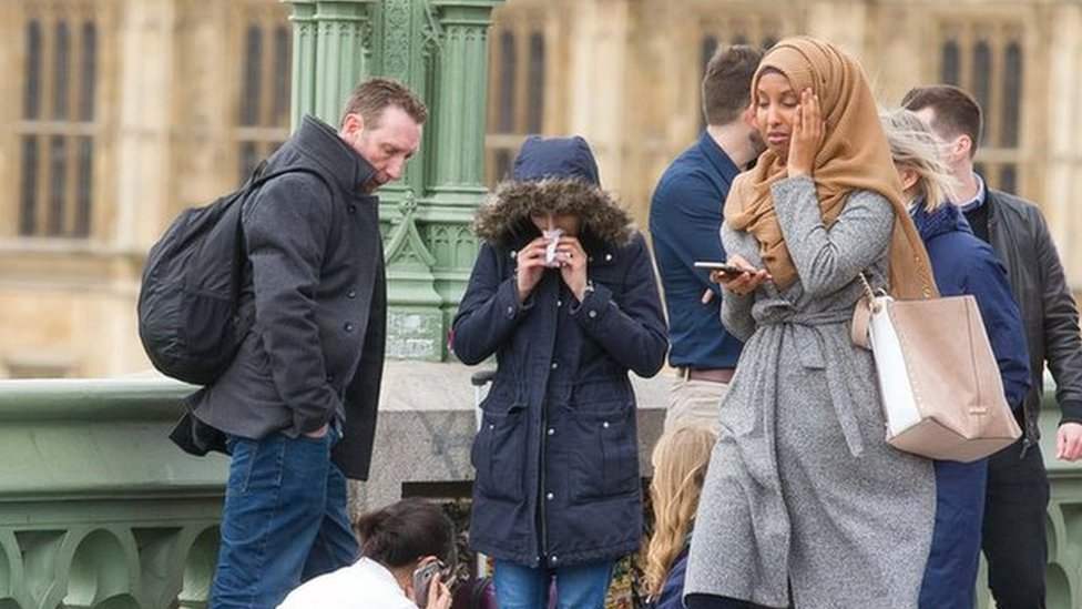 Muslim woman walking next to an injured person