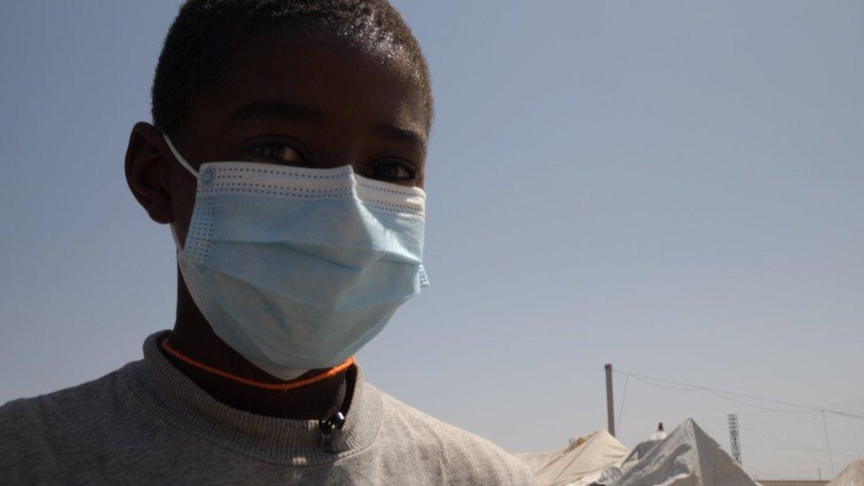 صبي في المخيم يرتدي كمامة وجه