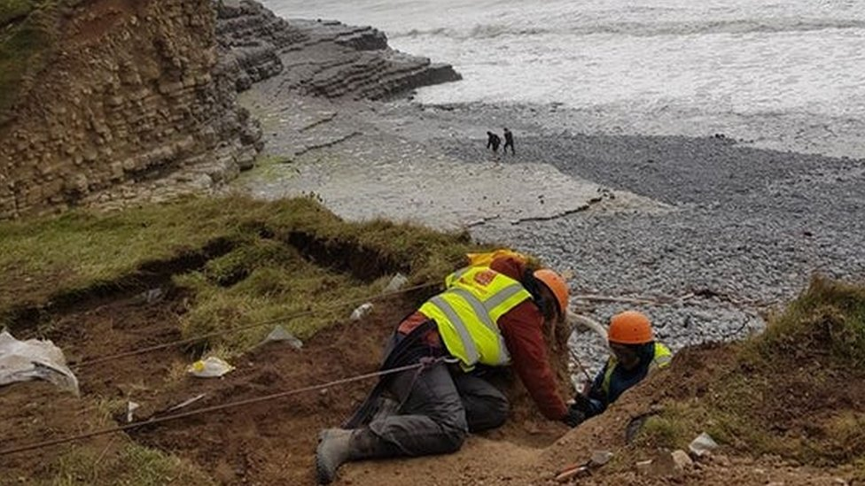 Experts attached to ropes excavate the remains from the top of the cliff ledge