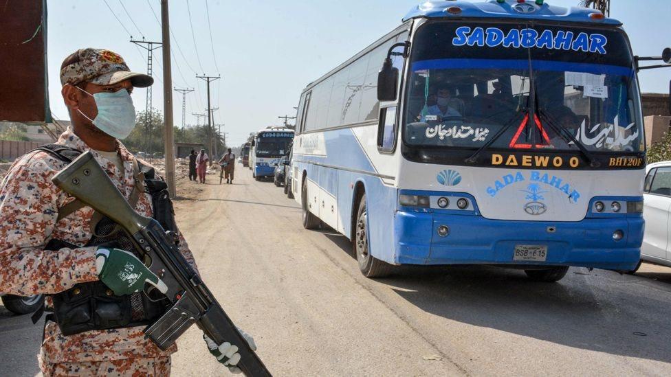 عسكري و حافلات تحمل ركابا