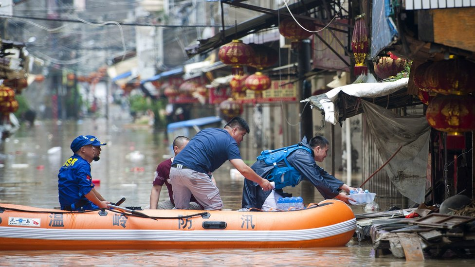 Rescuers distribute drinking water along flooded street in Wenling, eastern China's Zhejiang province on August 10, 2015