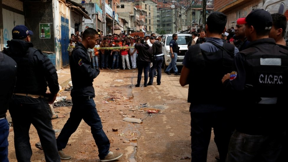 Police officers and criminal investigators look for evidence in front of a bakery, after it was looted in Caracas