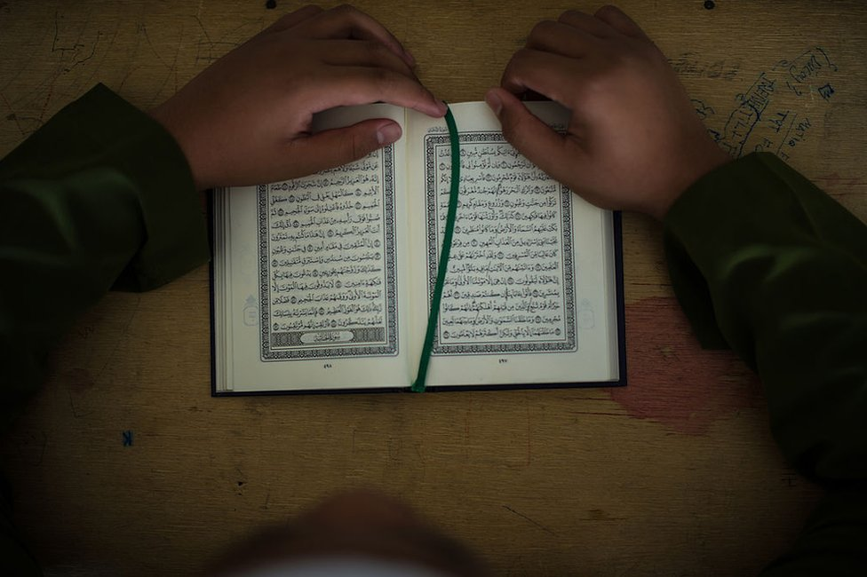 A Malaysian Muslim boy reads the Koran during a Koran lesson at a mosque in Ampang, in the suburbs of Kuala Lumpur on 30 July 2013.