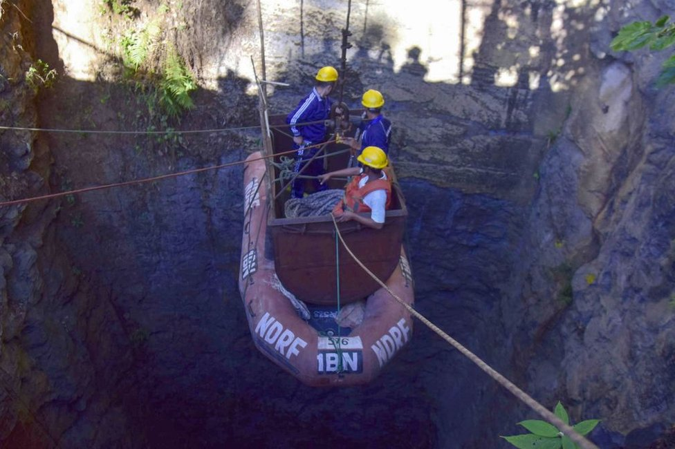 Indian navy divers go down into the mine with a pulley during rescue operations.