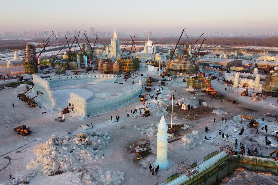 Pekerja membangun struktur es di lokasi Festival Es dan Salju Internasional Harbin