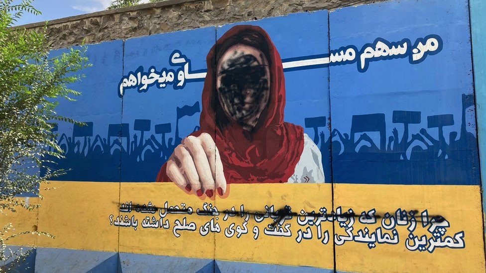 A blackened mural painting showing a female face in Kabul