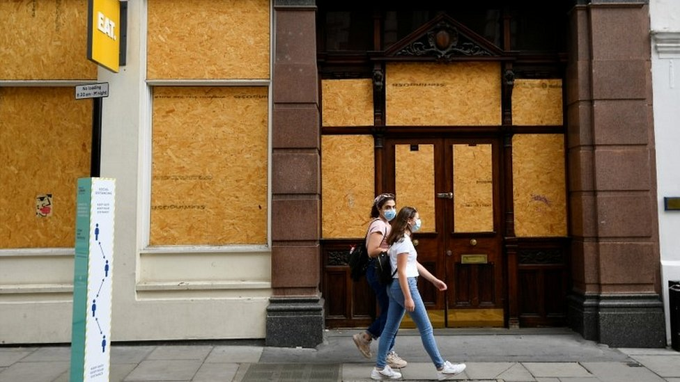 Women walking past boarded up London cafe