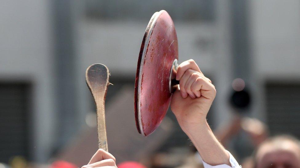 Cucharón de madera golpeando la tapa de una olla.