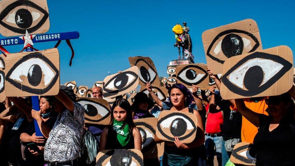 manifestantes sostienen carteles con ojos en reproche de lesiones oculares