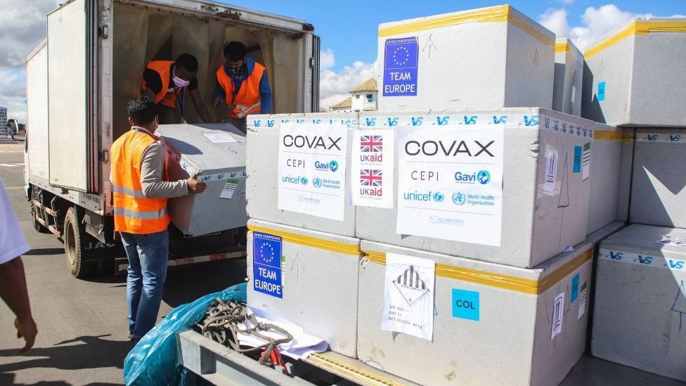 Boxes of Covax deliveries being unloaded by men in high-vis jackets