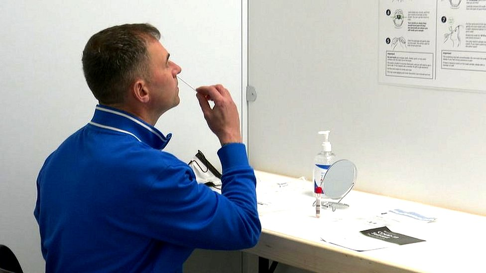A patient carries out his own Covid-19 test at a new walk-through testing site in Inverness
