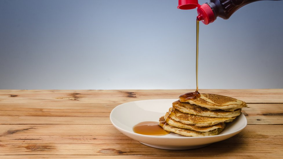 Maple syrup being poured onto pancakes