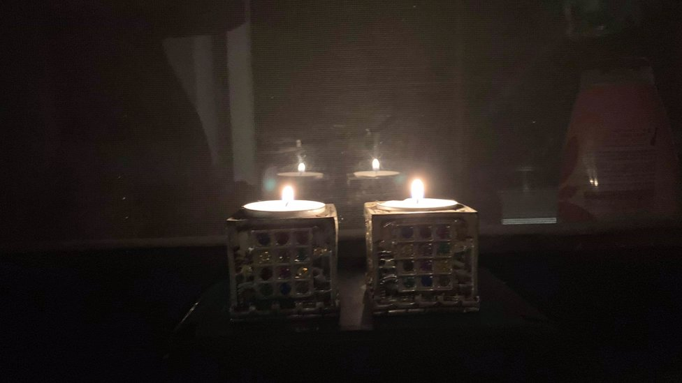 A pair of candles shine brightly in a dark room to commemorate Kristallnacht