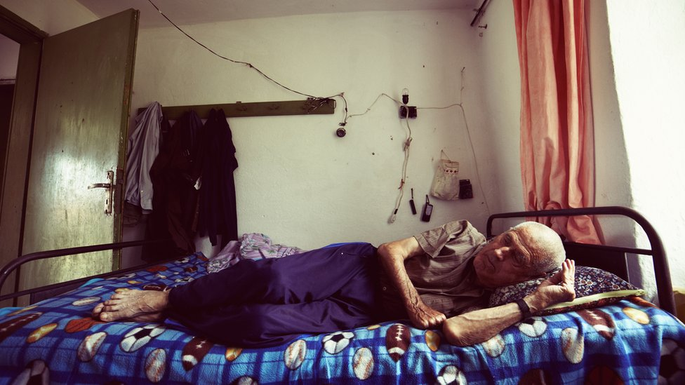 Idoso deitado na cama em ambiente insalúbre