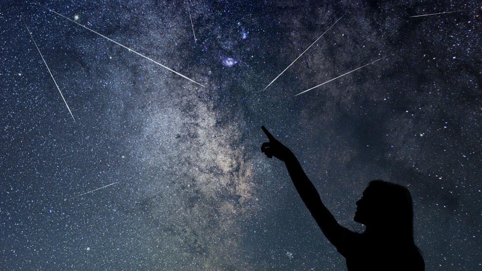 Mujer apuntando a estrellas fugaces en el cielo