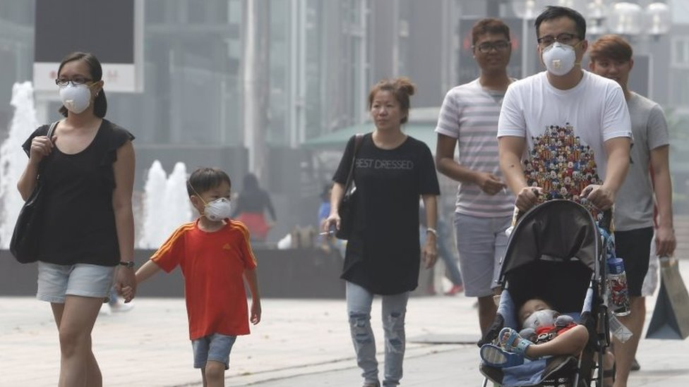 A family wearing masks walk at the haze-shrouded shopping district of Orchard Road in Singapore September 24, 2015.