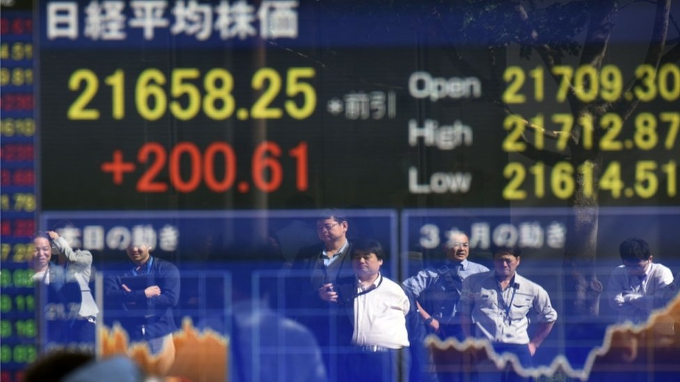 Pedestrians reflected in window with stock market figures in Tokyo on 23 October after Abe is elected