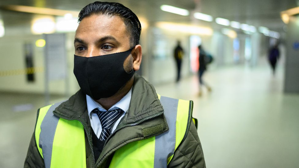 Man waring face covering in high visibility uniform