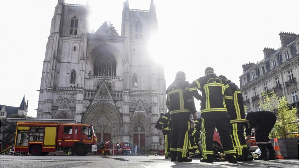 Firefighters are pictured in front of the cathedral