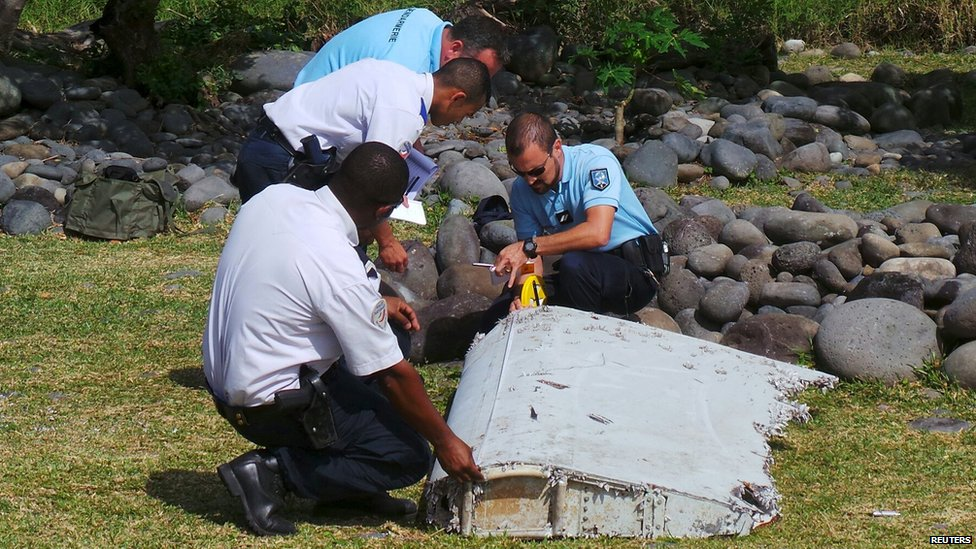 French gendarmes and police inspect a large piece of plane debris which was found on the beach in Saint-Andre, on the French Indian Ocean island of La Reunion (29 July 2015)