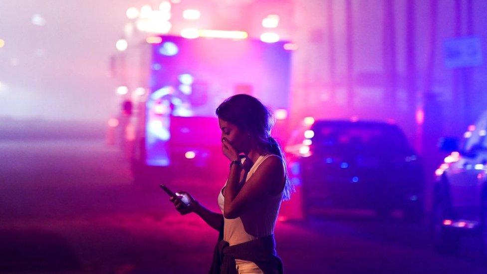Una mujer mira su celular con un camión de bomberos al fondo