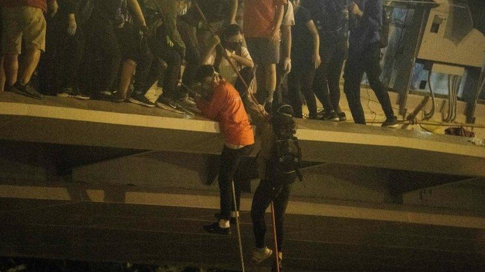 逃離理工大學校園的抗議者用繩索從橋上滑降至公路,並乘坐接應的摩托車離開。