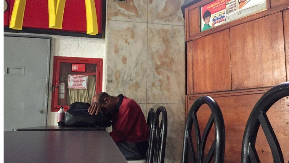 Un hombre descansando con la cabeza apoyada en una mesa.
