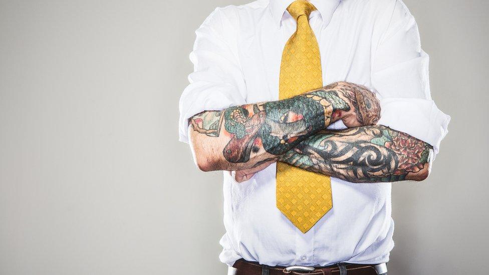 Hombre con tatuajes, camisa y corbata