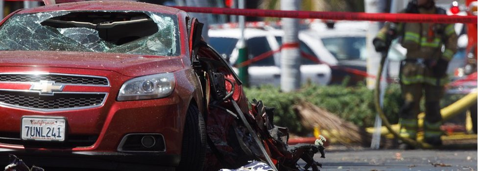 A car shows the damage after it was hit by a small plane that crashed into a strip mall parking lot in Santa Ana