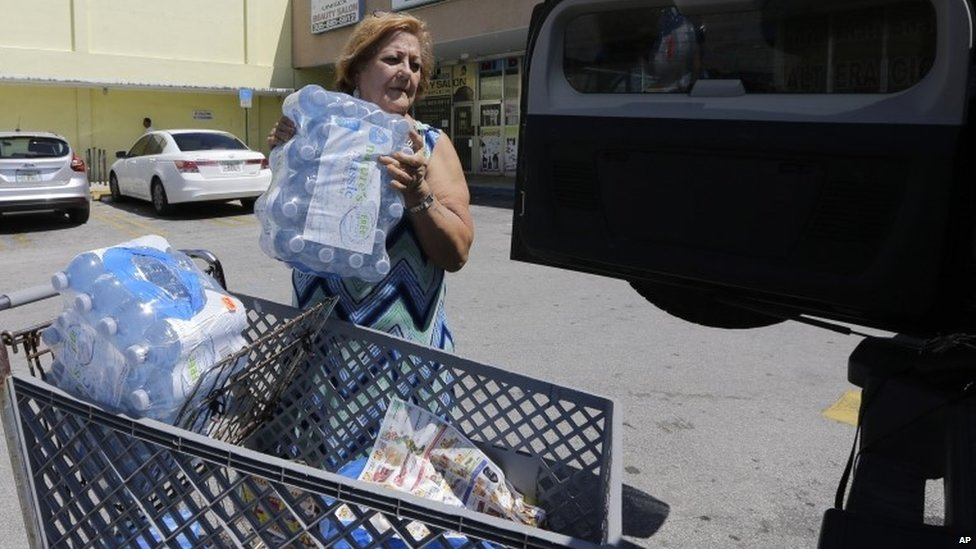 Rosa Monzon loads water bottles into her car as she prepares for Tropical Storm Erika
