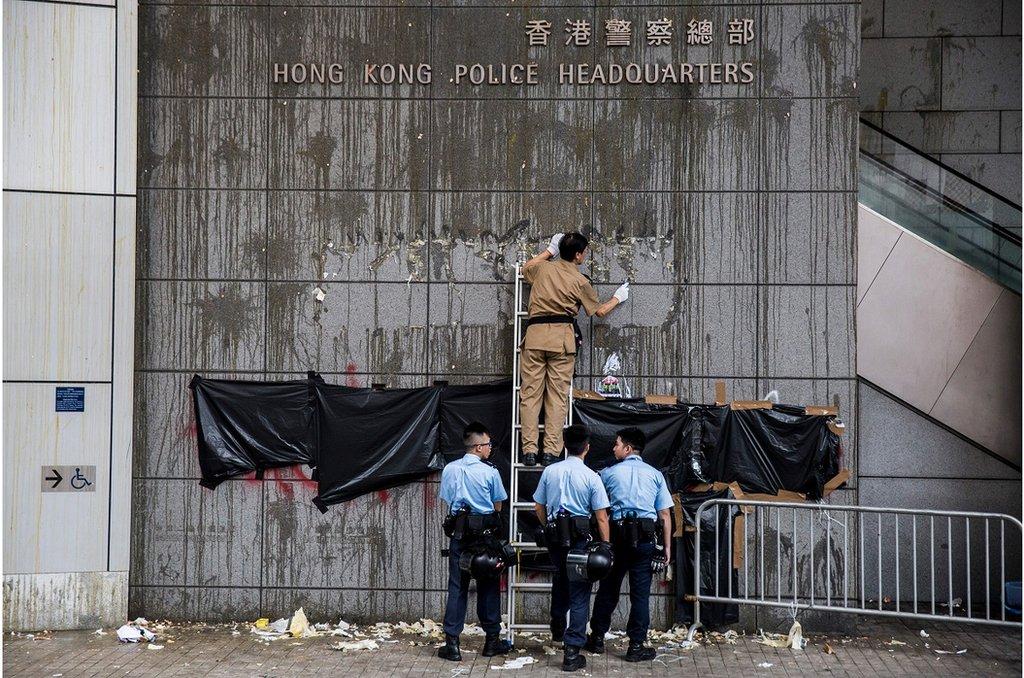 香港警察總部被大批示威者包圍,外牆牆面被示威者投擲雞蛋,警方派人清理。