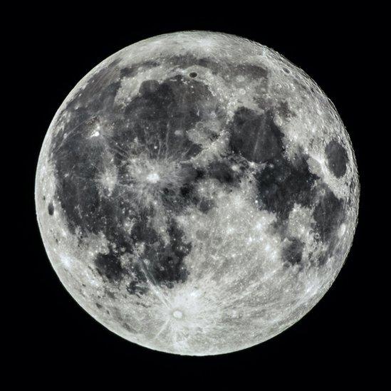 Luna llena con muchas características lunares visibles, como cráteres, crestas y mares.
