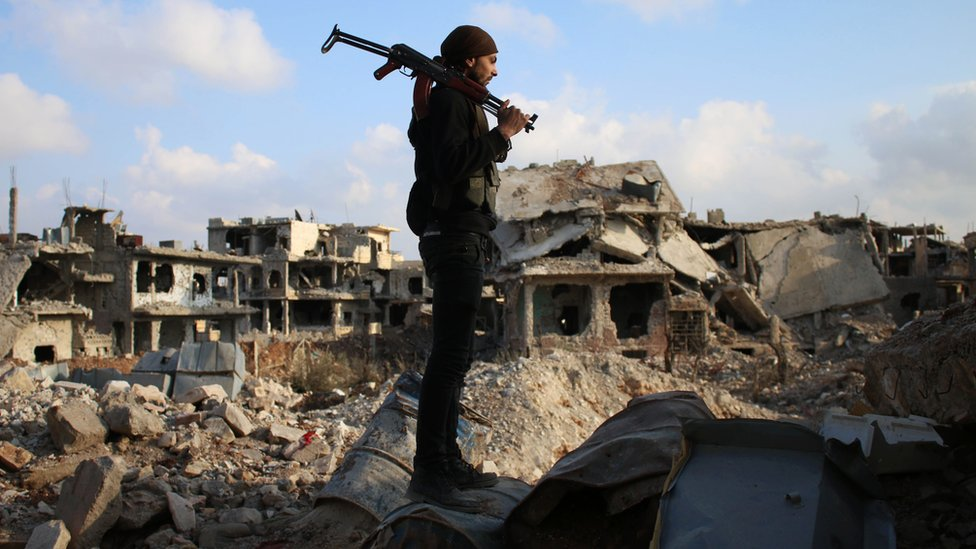 A rebel fighter stands amid the rubble of destroyed buildings in the rebel-held area of Deraa, in southern Syria, on 14 March 2017