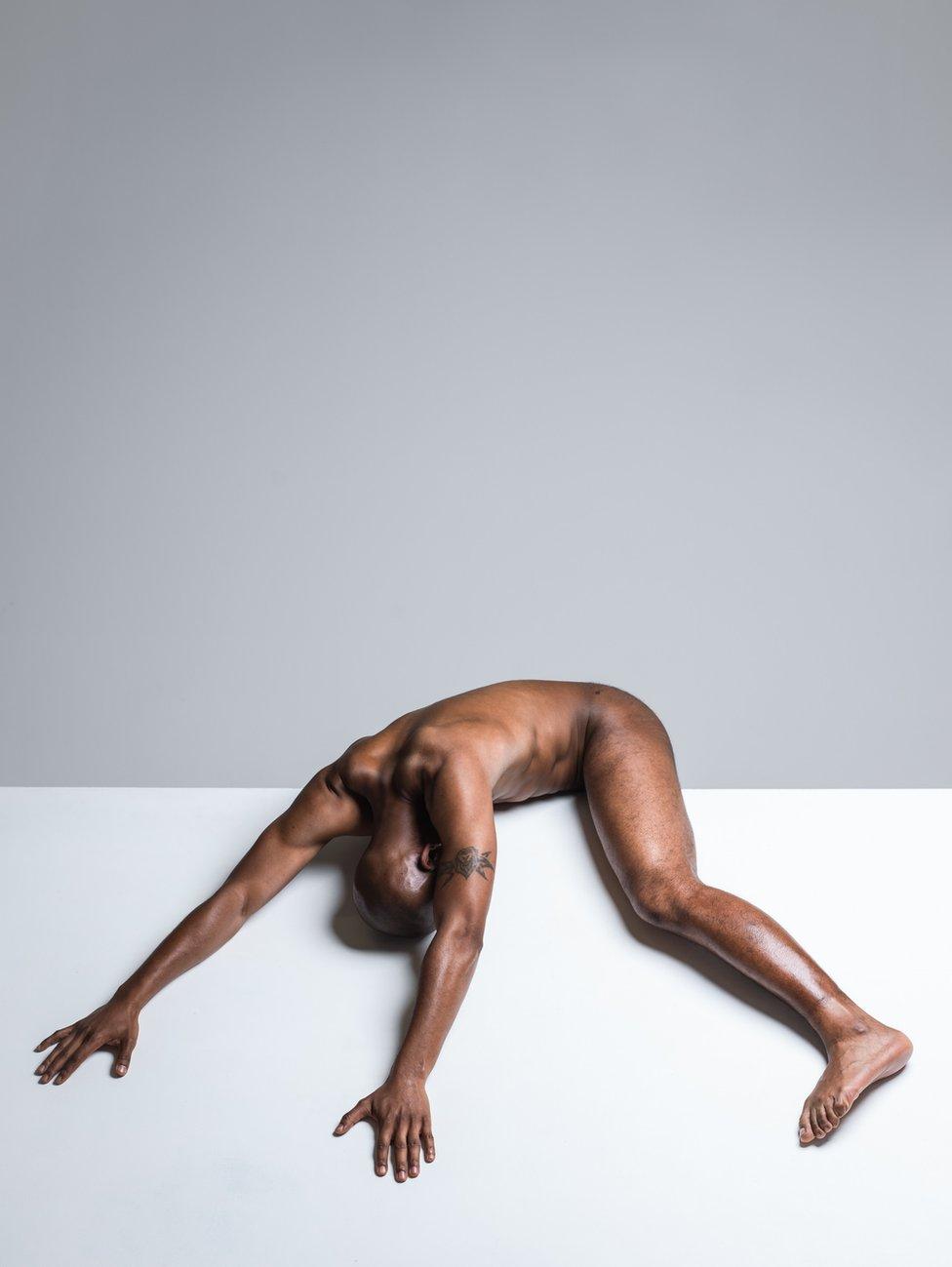 A nude drapes himself over a ledge.