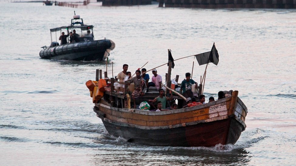 A wooden boat carrying Rohingya refugees including many children being detained by the authorities off the coast of Malaysia