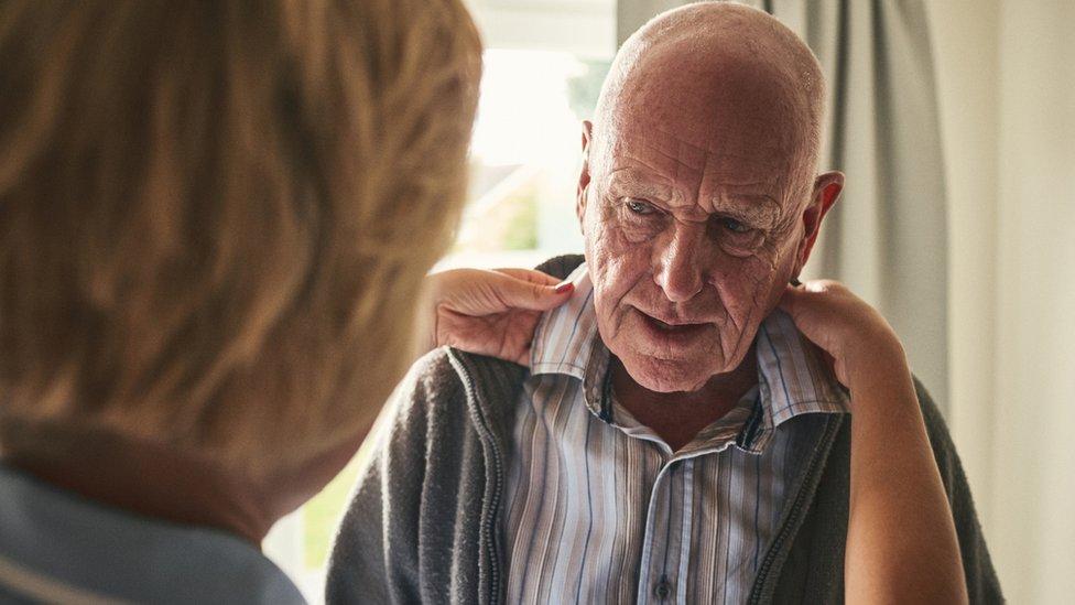Anciano al que ayudan a vestirse.