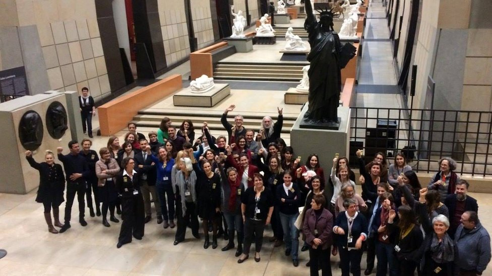 Group of female and male employees in the atrium of musee d'orsay raise hands in show of solidarity