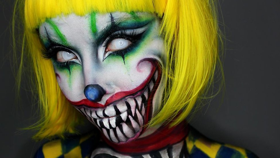 Ellie turns herself into a spooky clown with green eye makeup, an acid yellow wig and a scary toothy red smile painted on her face