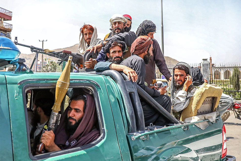 Taliban fighters are seen on the back of a vehicle in Kabul, Afghanistan, on 16 August