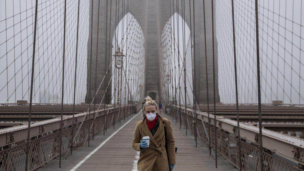 A woman wearing a mask walks the Brooklyn Bridge on 20 March 2020 in New York City