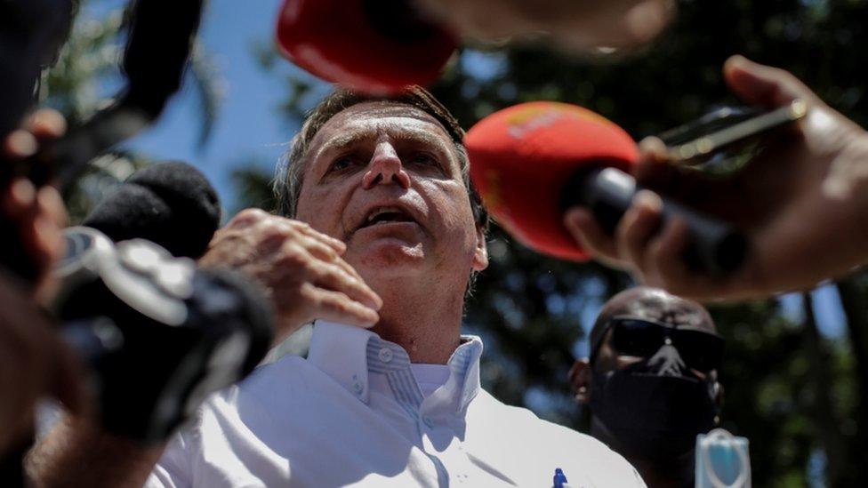 Bolsonaro fala, rodeado por microfones e sob céu azul