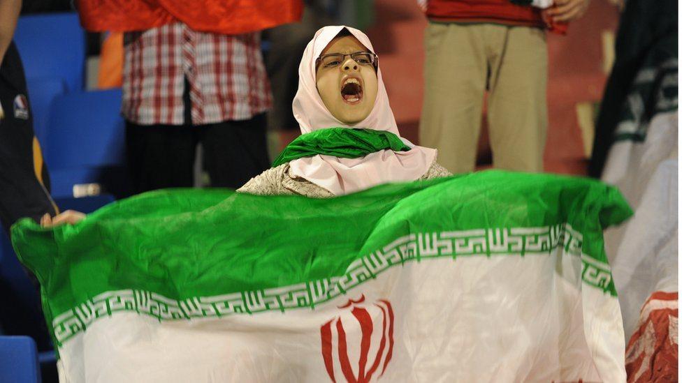 فتاة تحمل علم إيراني في مباراة بين إيران والسعودية
