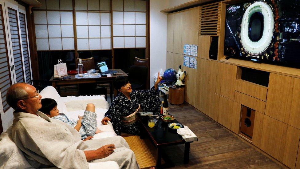 أسرة يابانية تشاهد حفل الافتتاح عبر التلفزيون