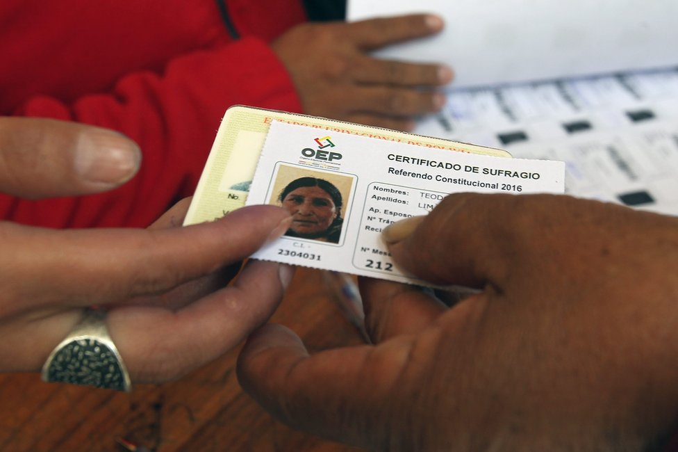 A woman receives a voting certificate in La Paz, 21 February