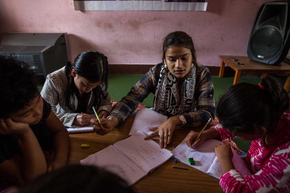 Seorang guru membimbing anak-anak perempuan yang diselamatkan dari perdagangan manusia di rumah persembunyian Shakti Samuha, pada 2018.