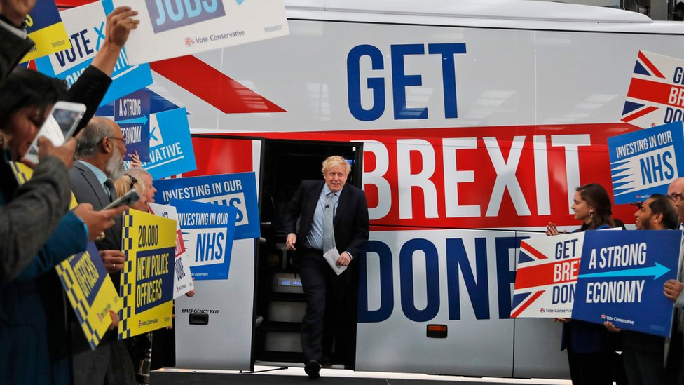 "Boris Johnson comes out of a bus which bears the slogan ""get Brexit done"" in Union Jack colours"